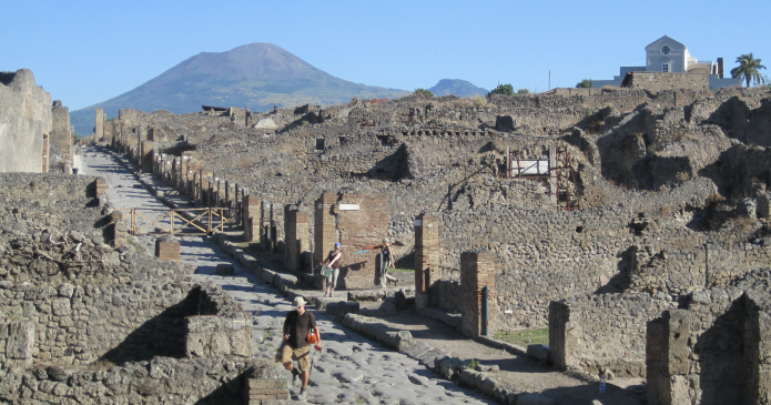 A view of Mt. Vesuvius from the Porta Stabia neighborhood in ancient Pompeii. There are standing walls made of stone and brick, and an ancient road in the foreground. People walk carrying equipment. In the back, a volcano and a modern building rise in front of blue sky.