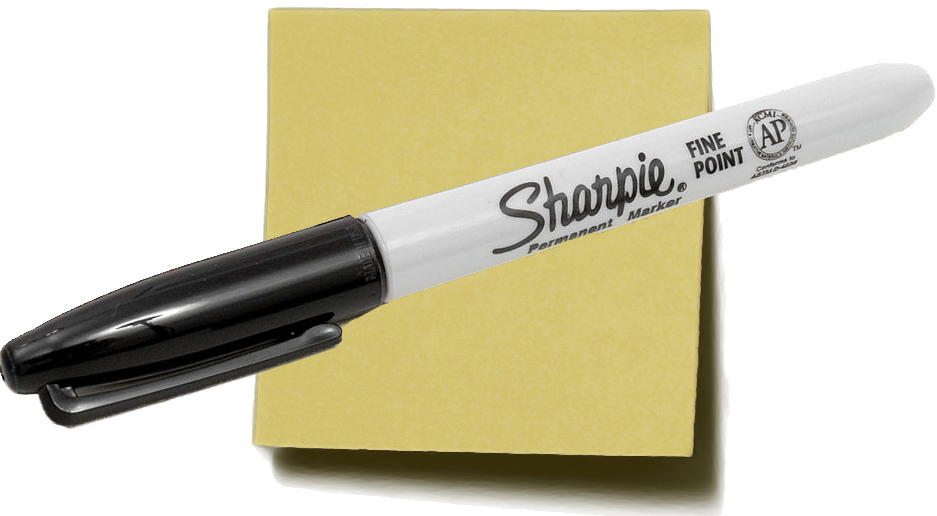A black sharpie marker sits atop a yellow sticky note.